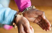 A Black child's wrist in handcuffs